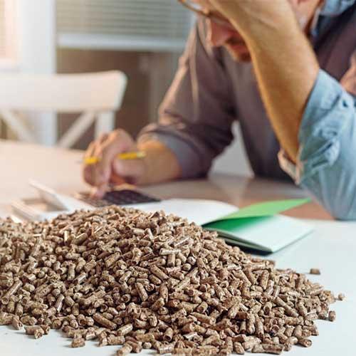 Hög av pellets (energikälla) på ett bord, person med miniräknare