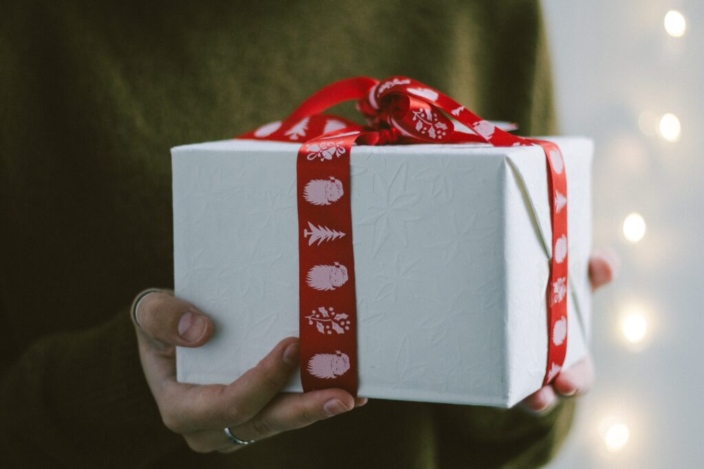 person som håller i ett vitt paket med röda snören.