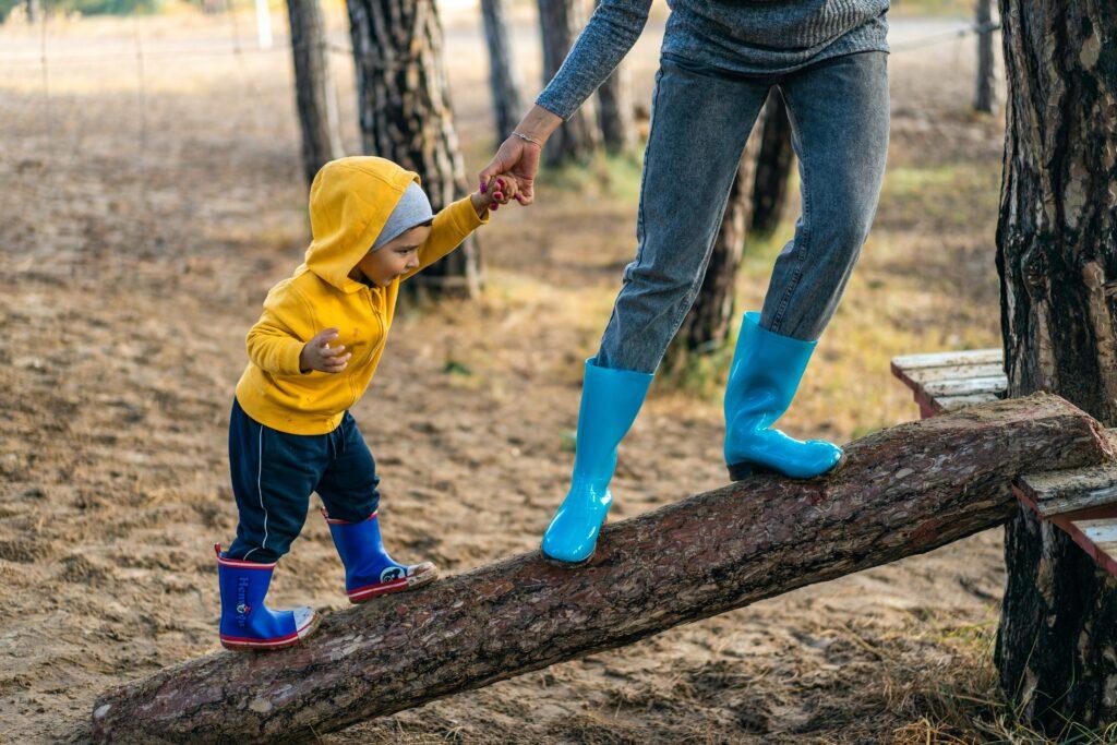 Litet barn i gul jacka som balanserar på trädstock med vuxen i handen