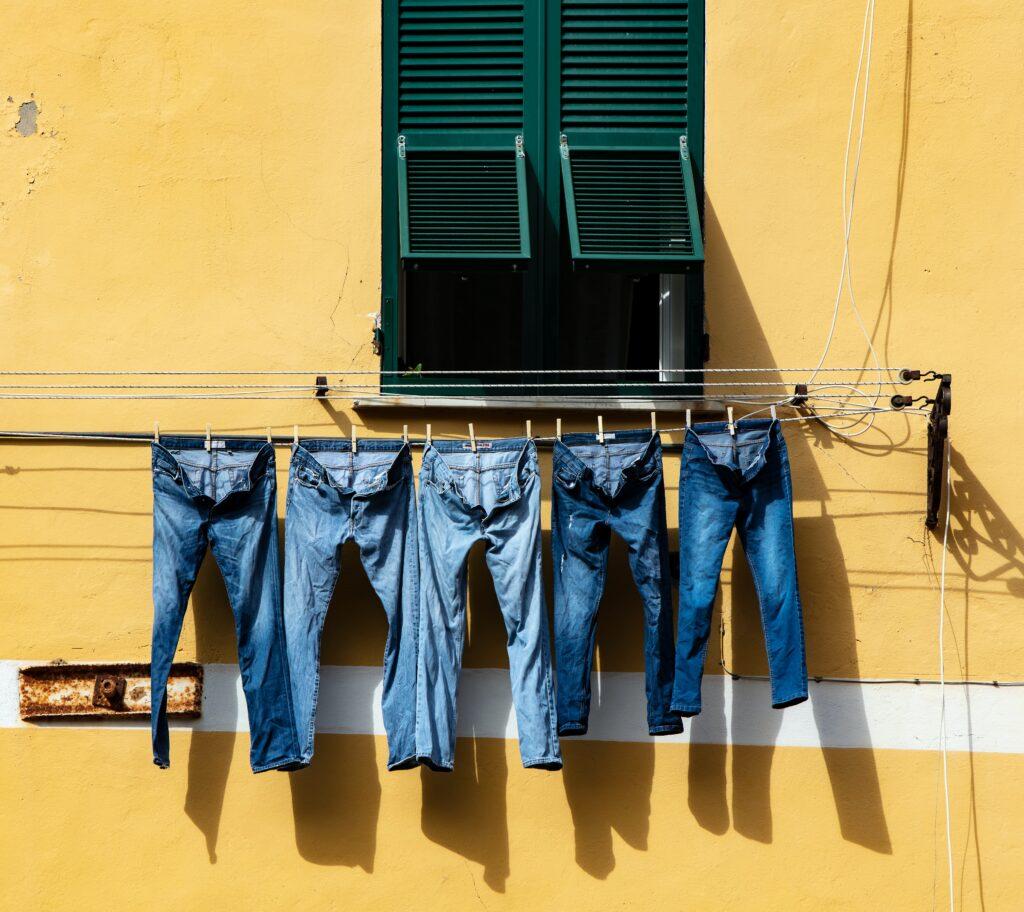Flera par jeans som hänger på tork framför en gul vägg