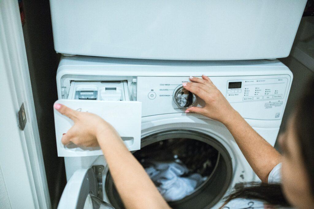 Tvättmaskin och person ställer in tvättprogram