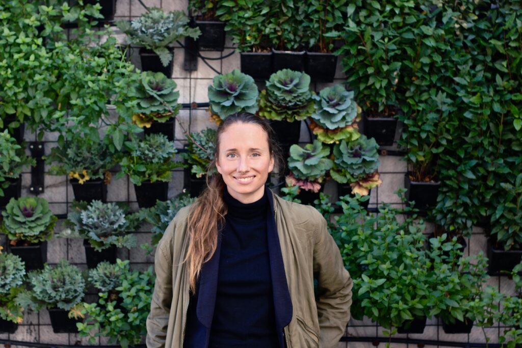 Leende kvinna framför en vägg täckt av växter. Bilden föreställer Hanna Olvenmark.